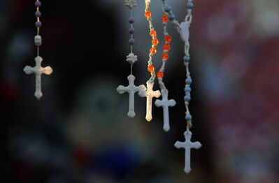 Rosaries are lit by the morning light on a makeshift memorial near the town Christmas tree in the Sandy Hook village of Newtown, Conn.,