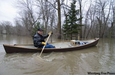 John Fulton paddles a canoe borrowed from his neighbours to take supplies over to his house, which is surrounded by overflowing waters from the Assiniboine River.