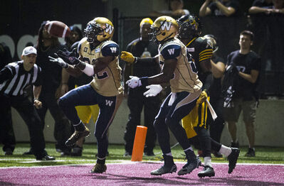 Winnipeg's Nic Grigsby (left) hauls in the game-tying touchdown with no time left on the clock Thursday night in Hamilton.