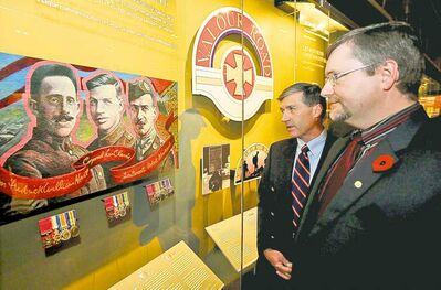 Erik Clarke (in rear), grand nephew of Victoria Cross recipient Cpl. Lionel Clarke, and Douglas Cargo, grand nephew of Victoria Cross recipient Sgt. Maj. Frederick Hall, look a the display of Victoria Cross medals on display at the National War Museum in Ottawa Monday.
