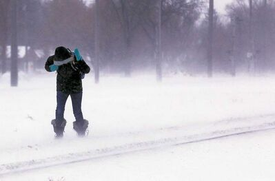 A pedestrian fights the high north wind in River Heights Friday as conditions worsen.