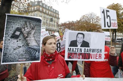 Lucie Morillon, head of research at French watchdog of Reporters Sans Frontieres (Reporters without Borders) holds a banner depicting Syrian human rights activist Mazen Darwish during a protest against violence in Syria, in Paris, Saturday, Oct. 20, 2012. Syria is one of the worst countries for press freedom, ranking 177 out of 180, according to a new Reporters Without Borders report.