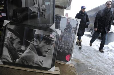 "FILE - This Jan. 22, 2010, file photo, shows festivalgoers walking past a poster of Robert Redford, far left, and Paul Newman in the film ""Butch Cassidy and the Sundance Kid"" during the Sundance Film Festival in Park City, Utah. A conservative Utah group believes the Sundance Film Festival's lineup featuring 'obscene' movies is at odds with Utah's culture of family values, and wants the state to pull its financial backing. (AP Photo/Chris Pizzello, File)"