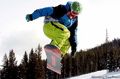A snowboarder catches a lot of air off a jump in the Rail Yard terrain park at Winter Park Resort.