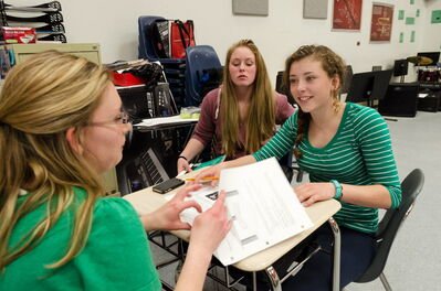 Teacher Lauren Marshall (left) speaks to students Taylor Byron and Jessica Forsyth (right). The graduation rate in Lakeshore School Division has risen from 50% in 2009 to 92% in 2013.