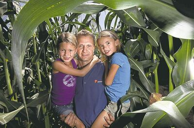 Phil Hossack / Winnipeg Free PressMyron Krahn, with his daughters Keira, 6, and Cadence, 7, is pumped over his  500-acre cornfield near Carman.