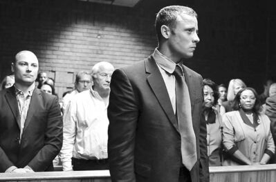 The Associated PressOscar Pistorius stands following his bail hearing, as his brother Carl (left) and father Henke (second from left) look on. He is accused of killing his girlfriend, Reeva Steenkamp, seen in photo at left.