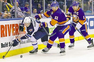 Jets� Alex Burmistrov is double-teamed by Islanders Frans Nielsen (51) and Mark Streit (2) in the third period.