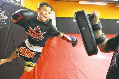 Connor Church, 10, works out  with Giuseppe DeNatale at the Canadian Fighting Centre. 'I just wanted them to be physically active,' says his father, Jason. 'We just fell in love with the sport.'