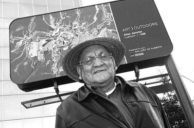 Alex Janvier stands in front of a billboard in Edmonton that features his painting, Lubicon.
