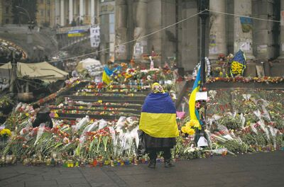 Emilio Morenatti / The Associated Press FilesA woman wearing a Ukrainian flag honours the fallen in Kiev�s Independence Square. �These people now in power had better produce results quickly.�