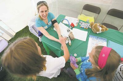 Dr. El Simons, an allergy specialist, helps out 10-year-old Afrika Small-Denbook�s teddy bear
