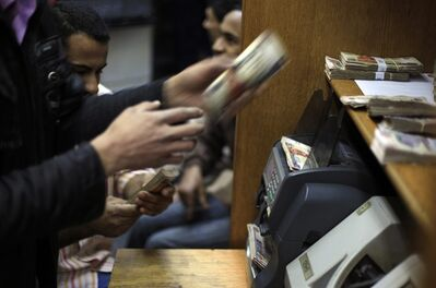 Egyptians count money at a currency exchange office in downtown Cairo, Egypt, Jan. 2, 2013. THE CANADIAN PRESS/AP, Khalil Hamra