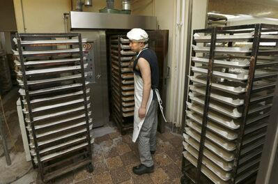 Baker Yuan Gao pulls a rack of cakes out of the oven.