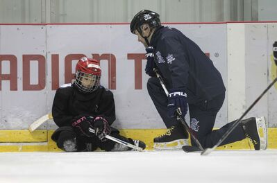 Murray Cobb, Director of the Winnipeg Jets Hockey Academy, works with Jennifer. ( Ruth Bonneville / Winnipeg Free Press)