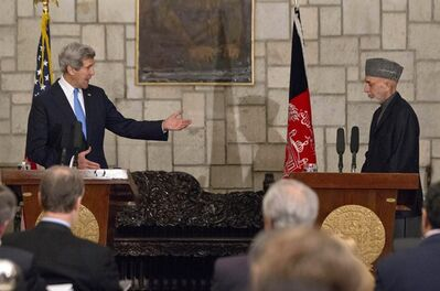 "Secretary of State John Kerry gestures towards Afghan President Hamid Karzai during their joint news conference at the Presidential Palace in Kabul, Monday, March 25, 2013. Kerry and Karzai made a show of unity Monday, shortly after the U.S. military ceded control of its last detention facility in Afghanistan, ending a longstanding irritant in relations between the two countries. Kerry, in Afghanistan for an unannounced visit, said he and Karzai were ""on the same page"" when it comes to peace talks with the Taliban. (AP Photo/Jason Reed, Pool)"