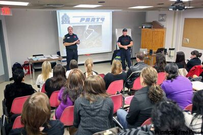 Brandon Police Service school resource officer Const. David Scott, right, along with City of Brandon fire inspector Richard McCurry, addresses a group of students from Vincent Massey Collegiate last year. The Progressive Conservatives have pledged to expand the school resource officer program.