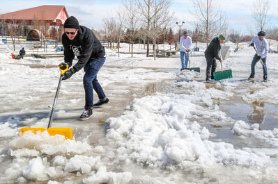 Colin Lambert, left, owner of Sk8 Skates at The Forks, made a Facebook event inviting users of the Plaza skatepark at the Forks to come today and help snow plow, shovel, ice chip and push water to get the park in dry usable condition as soon as possible in Winnipeg on Monday.