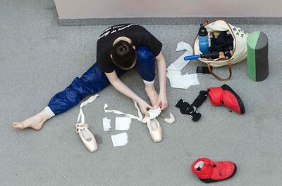 A dancer preps her ballet shoes.