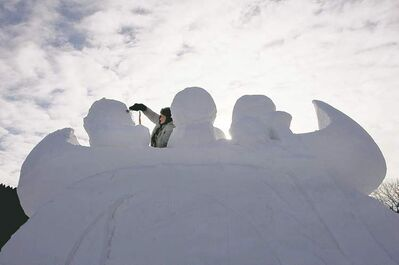 Snow sculptor Jacques Boulet carves a snow canoe and voyageur crew at the open air snow bar in Voyageur Park.