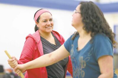 Christine Cyr (left) plays an Inuit wrestling game with Southeast Collegiate instructor Michelle Carriere.