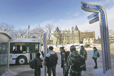Passengers wait at a bus stop across from the University of Winnipeg.