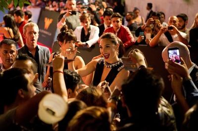 """FILE -- In this May 27, 2017 file photo, actress Gal Gadot signs autographs and greets fans during the Latin American premiere of the film """"Wonder Woman,"""" in Mexico City. For a country that takes pride in even the smallest successes of its international celebrities, the debut of Wonder Woman has sparked an Israeli lovefest for homegrown hero Gadot. (AP Photo/Rebecca Blackwell, File)"""