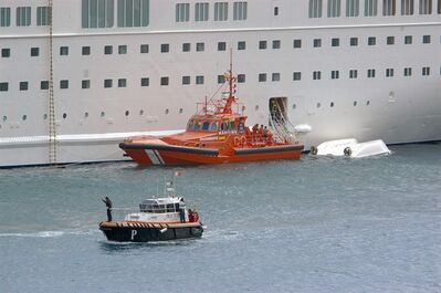 An orange rescue boat is seen docked by a capsized lifeboat from the British-operated cruise ship Thomson Majesty in Santa Cruz port of the Canary Island of La Palma, Spain, Sunday Feb. 10, 2013. The lifeboat from the Thomson Majesty fell into the sea at port in Spain's Canary Islands, killing five people and injuring three others Sunday, officials said. Rescue personnel were called to the dockside after a lifeboat with occupants had fallen overboard from a cruise ship. Spanish national broadcaster RTVE said an emergency training drill was taking place at the time of the accident. (AP Photo/Manuel Gonzalez)