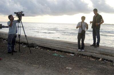 In this photo taken on Monday June 11, 2012 veteran Middle Eastern TV reporter Baker Atyani, right, prepares to tape a segment of his report by the sea wall in Jolo, the capital of the island province of Sulu in Southern Philippines about 950 kilometers (590 miles) south of Manila, Philippines. Atyani, a Jordanian national who met and interviewed Osama Bin Laden and his aides in Afghanistan months before the Sept.11, 2001 attacks and now Al-Arabiya's TV Bureau Chief for Southeast Asia based in Jakarta, has disappeared with the two Filipino crew (also in the photo) on a restive Jolo island where militants are active, officials said Friday June 15, 2012. (AP Photo/Nickee Butlangan)