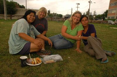 Gifts of Grace co-founders Kendra Jackson (second from left) and Kim McIntyre (second from right) have a chat with Nikki (left) and Julie (right) at the organization's second anniversary barbecue at the corner of Austin Street and Henry Avenue on Aug. 21.