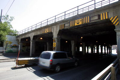 A minivan drives under the Main Street underpass at Higgins Avenue.