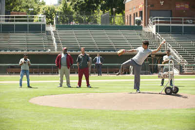 Special delivery: Bill Paxton (red pants) and Greg Alan Williams (red jacket) watch Suraj Sharma pitch as Pitobash (left) videotapes. Jon Hamm and Madhur Mittal (far right) check out his form.