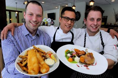 Grove general manager Carew Duffy and chef Norm Pastorin and sous-chef Blair Schreyer pose with fish and chips and braised duck leg.