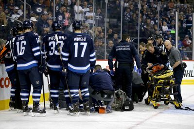 Winnipeg Jets defenceman Jacob Trouba lays on the ice as he is tended to by emergency personnel after going hard into the boards head first in the second period.