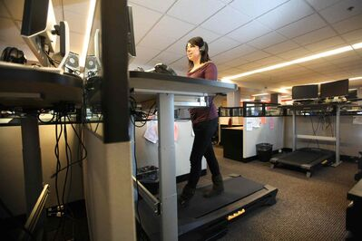 Dietitian Lise Timmerman walks on a treadmill while talking on the phone with a client. She plans to keep using the machines after the research project is done.