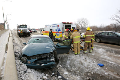09122013Brandon Fire and Emergency Services members move a patient on a stretcher to a waiting ambulance after a two-vehicle collision on the Daly Overpass in Brandon on Monday afternoon. At least two patients were taken to hospital. Their conditions have yet to be released by the Brandon Police Service. (Tim Smith/Brandon Sun)