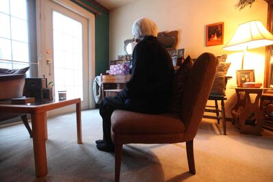 A women sits next to her piano where a large bag of wrapped Christmas gifts were stolen from her home Friday morning while she was in her basement loading groceries from a recent trip to the store.