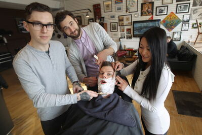 Dru Barrow (from left), Mason Melle and Kim Nguyen give Hunter & Gunn Barbershop owner Jeremy Regan a shave.