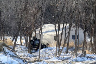 A tent used by the Brandon Police Service stands near the banks of the Assiniboine River in Queen Elizabeth Park on Wednesday afternoon while they investigate the discovery of a body.