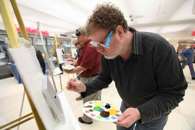 "Doug Speirs tries to paint a picture of his late Bassett hound, Cooper, at the ""Eye on the Arts"" Blind Media Painting Challenge at Winnipeg Square Tuesday.  Speirs was wearing a set of glasses (under his own glasses) that prevented him from seeing normally to bring awareness to what it's like to have a vision impairment."