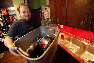 Scott Wachal loads his dirty dishes into a container at his Cathedral Avenue home Monday. Wachal's water pipes are frozen and he hasn't had water for two weeks.
