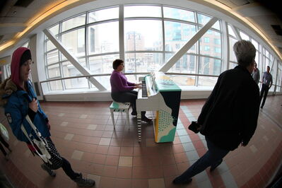 Erna Wiens is the first to play a donated piano in public, on the walkway between Portage Place and the Bay Tuesday.