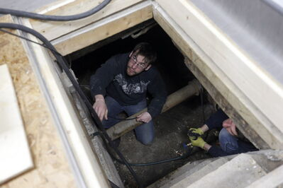 Chase Loewen works in a tight subfloor crawl space on shop's frozen  waterlines.