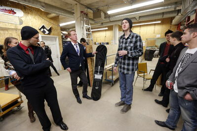 Red River College's Scott MacAulay holds a snowboard as he stands next to snowboard maker Matt Olson (in tuque) at AssentWorks/Ramp-Up Manitoba on Friday during the Start-Up Bus Crawl.