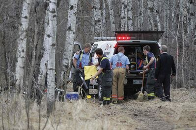 Firefighters battle a grass fire in the Assiniboine forest Sunday.