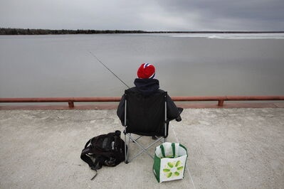 Kyle Otter tries his luck by throwing his line in a thawed section of Lake Winnipeg.