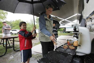 Kim Macaulay cooks under Tristan Szajewski's umbrella as his cousin, Ethan, looks on at the Birds Hill Park campsite Sunday.