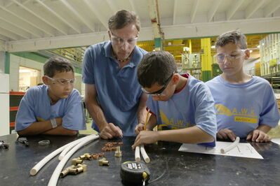 Triplets (from left) Graeme, Gabe and Andrew Perrie learn about plumbing from instructor Dwaine Gautier.