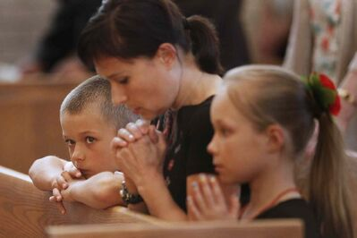 People attend a memorial service at St Joseph Ukrainian Catholic Church Sunday for victims of Malaysian flight MH17.