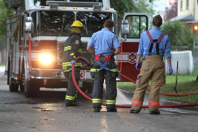 Fire crews wash down the scene of a stabbing that occurred early Saturday morning in front of 590 Spence St.